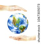 hands holding the earth.... | Shutterstock . vector #1067305073