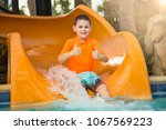 cute happy boy riding down a... | Shutterstock . vector #1067569223