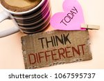 Small photo of Text sign showing Think Different. Conceptual photo Rethink Change on vision Acquire New Ideas Innovate written on Tear Cardboard Piece on the plain background Pink Heart and Coffee Cup.