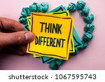 Small photo of Handwriting text Think Different. Concept meaning Rethink Change on vision Acquire New Ideas Innovate written on Sticky Note Paper Holding by man plain background on Heart Paper Balls.