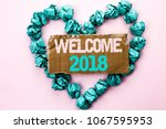 Small photo of Writing note showing Welcome 2018. Business photo showcasing Celebration New Celebrate Future Wishes Gratifying Wish written on Tear Cardboard on Plain background on Heart Paper Balls.