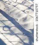 Small photo of Shadows on the snow.Abstract background.Traces of animals on white snow.Bestial path.Fresh snow fell.