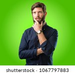 Small photo of Young hipster man with big beard doubt expression, confuse and wonder concept, uncertain future over green background