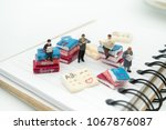 Small photo of Miniature people: Business team sitting on book, reading news paper with copy space using as background business teamwork, education, problem and solve and vision concept.