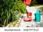 Little girl in a garden with green watering pot - stock photo