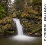 Small photo of Waterfall on long exposure in colorful autumn forest, Schwarzwald, Germany