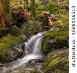 Small photo of Water flowing through moss covered fallen trees and rocks on long exposure in Schwarzwald Germany