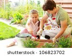 Elderly woman and child replanting flowers for better growth - stock photo