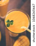 Small photo of Mango Lassi or yogurt, Indian popular summer drink served in glass with whole Alphonso Aam fruit, selective focus