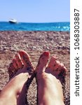 Small photo of Female feet with adherent small pebbles on the background of the sea