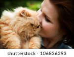 Young woman with Persian cat playing. Outdoors portrait - stock photo