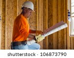 A male construction worker reads blueprints while working at a construction site - stock photo