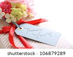 Present and bouquet with thank you Card in handwriting - stock photo