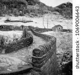 Small photo of black and white close up view of historic stone bridge from Roman times in a secluded mountain valley