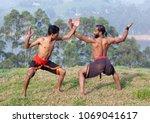 Small photo of Indian fighters performing Adi Thada (Hand Combat) during Kalaripayattu Marital art demonstration in Kerala, South India
