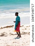 Small photo of Diani Beach, Mombasa, Kenya - 10.30.2017: Single black kenyan male wearing traditional masai clothing using a smartphone while walking on the white sand beach.