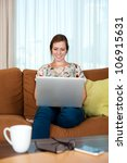 A young woman on a couch, happy on her laptop. - stock photo