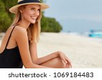 Small photo of Sideways shot of beautiful delighted woman with tanned healthy skin, wears swim suit and straw hat, spends free time at sandy beach, satisfied to spend summer vacation at resort paradise place