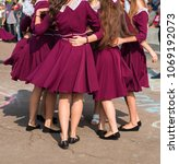 Small photo of elegant high school graduates in the same dresses of marsala dance a waltz in the schoolyard