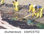 CIRCA 1990 - A team of environmentalists clean up an oil spill in Huntington beach, California - stock photo