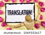 Small photo of Handwriting text Translation Motivational Call. Concept meaning Transform words or texts to another language written on Sticky Note Paper within Paper Balls on plain background Wooden Robot Toy.