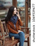 Small photo of Make a pause. Concentrated girl crossing legs while sitting on the bench and talking per telephone