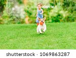 Stock photo dog with ball in mouth runs from kid playing chase game at summer lawn 1069863287