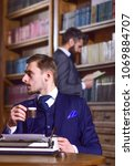 Small photo of Men in suits in library with antique books on background, defocused. Retro writer concept. Writer or author with typewriter looks for inspiration for new book, drinks coffee in library with friend.