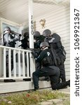 Small photo of Police tactical or swat team gathered round the door of a house with drawn weapons and protective clothing simulating an arrest or hostage stand-off situation