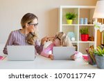 mother and daughter sitting at... | Shutterstock . vector #1070117747