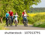 Family with three girls having a weekend excursion on their bikes on a summer day in beautiful landscape - stock photo