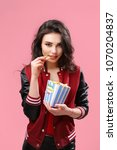 Small photo of Alluring young brunette in popcorn bag looking playfully at camera having bite on pink background.