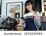 young asian woman barista using ... | Shutterstock . vector #1070250983