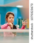 Small photo of little serious girl playing table tennis in the tennis hall, tennis racket hitting the ball, the pitch of the ball