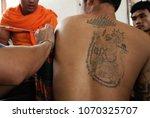 Small photo of WAT BANG PHRA, Nakhon Prathom, THAILAND - FEB 27 2010: Unidentified master make Thai traditional tattoo (Yantra) on body's adherent during Memorial ceremony Master Day Wat Bang Pra, Thailand.