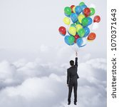 Small photo of Businessman flying with balloons on abstract cloudy sky background with copy space. Success and opportunity concept