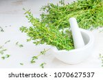 Thyme twigs in the pounder on white wooden table. Food foto