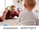 young father lying on floor... | Shutterstock . vector #1070771873