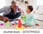 dad and toddler son having fun... | Shutterstock . vector #1070794313