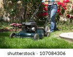 Woman is mowing her lawn with lawn mower in her back yard - stock photo