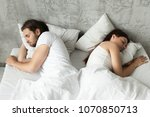 Stock photo unhappy indifferent couple sleeping separately back to back keeping distance lying in bed at home 1070850713