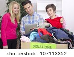 volunteer group with clothing donation and tablet - stock photo