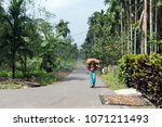a man carries a big bag on his... | Shutterstock . vector #1071211493