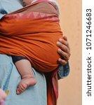 mother carries her baby in a... | Shutterstock . vector #1071246683