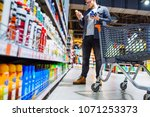 man can't decide in store what... | Shutterstock . vector #1071253373