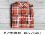 folded orange tartan shirt on... | Shutterstock . vector #1071291017