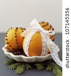 Close up of oranges pinned with cloves and wrapped in lace - stock photo