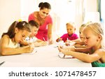 Small photo of Smiling diligent kids learning to write on lesson in elementary school class