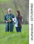 Small photo of Farmer with agronomist walking in agricultural field