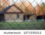 protected house behind fence | Shutterstock . vector #1071550313